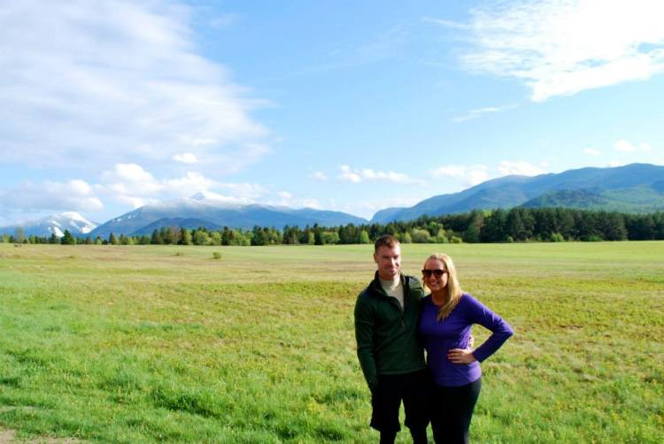 Standing in front of a field with mountains in the background.